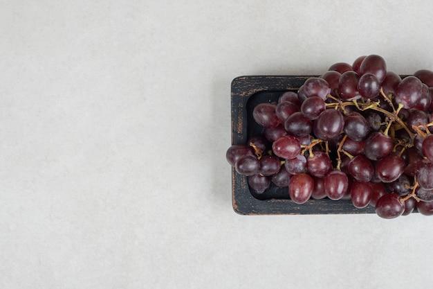 Verse rode druiven op zwarte plaat