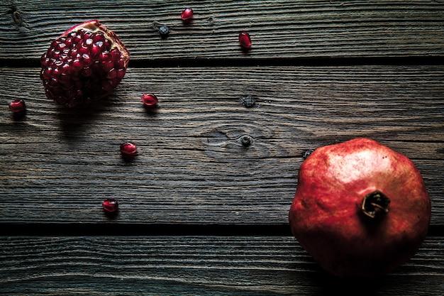 Verse rode granaatappel en grapefruit op een houten achtergrond. granaatappel in plaat op houten achtergrond. granaatappel op hout gestructureerde achtergrond. bovenaanzicht beeld.