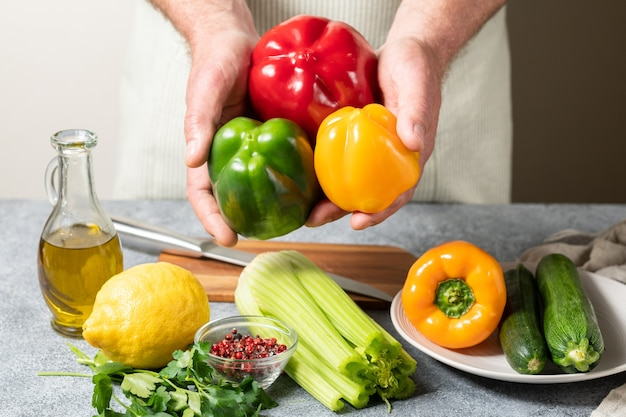 Verse rode groene en gele paprika courgette en selderij in de handen van de chef