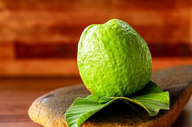 Verse rode guaves met groene bladeren op houten tafel. hout en guavebladeren.