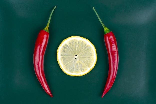 Verse rode hete pepers en citroen op een bord. vitamine gezond voedsel.