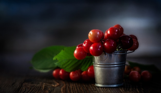 Verse rode kersen in kleine metalen emmer op oude houten tafel