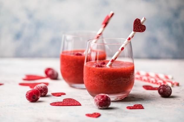 Verse rode kersenmargarita of daiquiri-cocktail met hart over grijze achtergrond, valentijnskaartdagconcepten