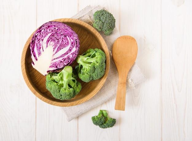 Verse rode kool en broccoli in de houten plaat. witte houten tafel met tafellaken. bovenaanzicht