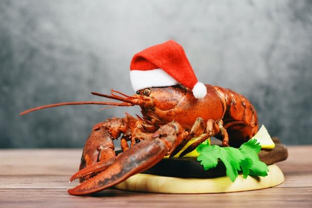 Verse rode kreeft met kerstmuts schelpdieren gekookt in het visrestaurant - gestoomd kreeftdiner eten op houten kersttafel instelling vieren in feestelijke feestdag winter