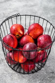 Verse rode nectarines in een stalen mand.