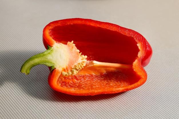 Verse rode paprika, gehalveerd, holte aan de binnenkant, zaden. close-up op een grijze achtergrond.