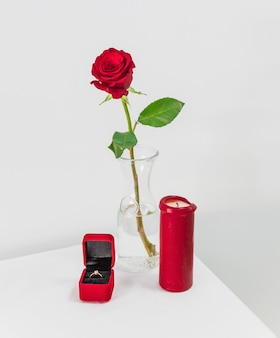 Verse rode roos in vaas en huidige doos met ring in de buurt van kaars op tafel
