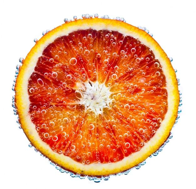 Verse rode sinaasappel valt in water