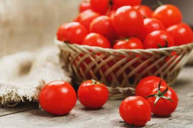 Verse rode tomaten in een rieten mand op een oude houten tafel. rijpe en sappige kerstomaten met druppels vocht, grijze houten tafel, rond een doek van jute. in een rustieke stijl.