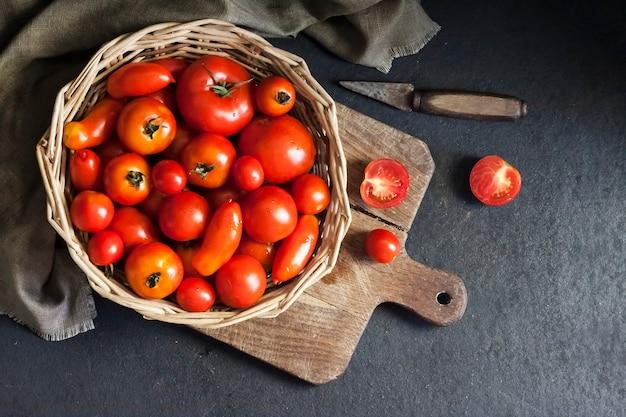 Verse rode tomaten in rieten mand op zwarte achtergrond. platliggend, bovenaanzicht