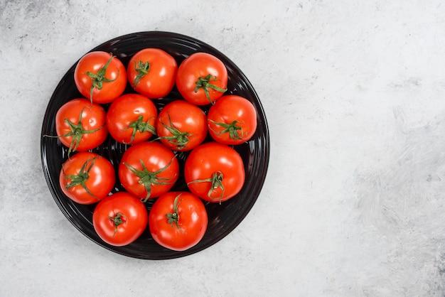 Verse rode tomaten op een zwarte plaat.