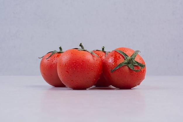 Verse rode tomaten op witte tafel.