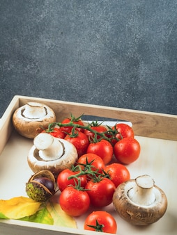 Verse rode tomaten; paddenstoelen en kastanje in houten bakje
