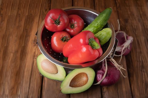 Verse rode tomaten, paprika, komkommers, rode uien en avocado op een houten achtergrond