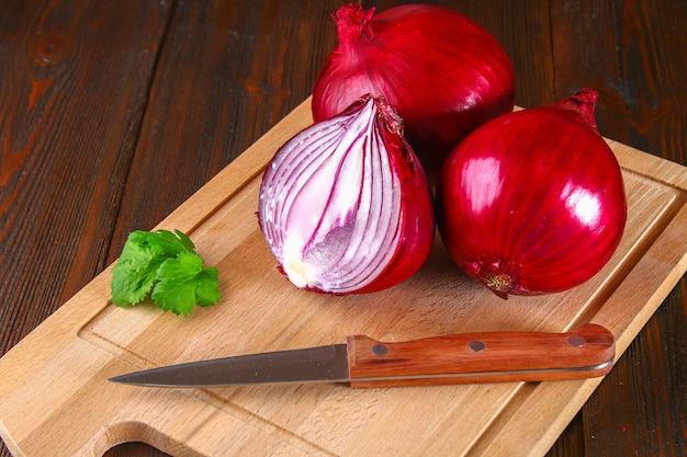 Verse rode uien en gehakte plakjes op een houten tafel.