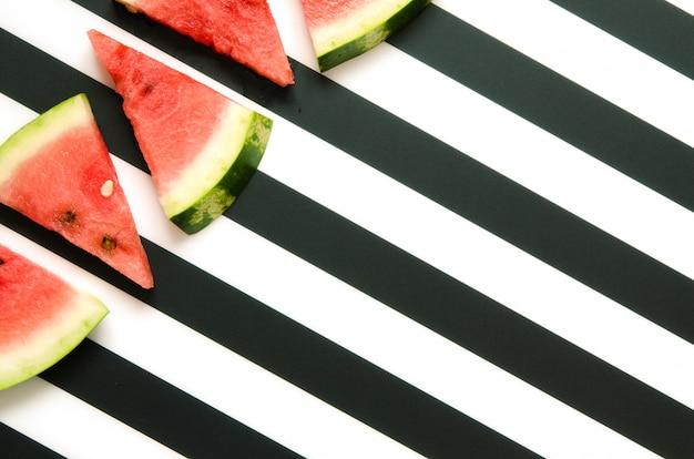Verse rode watermeloenplak op gestreepte achtergrond