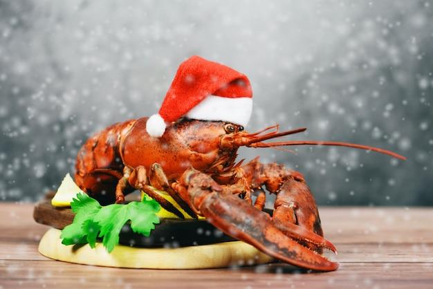 Verse rode zeekreeft met kerstmishoed bij kerstmislijst van het dinervoedsel het plaatsen