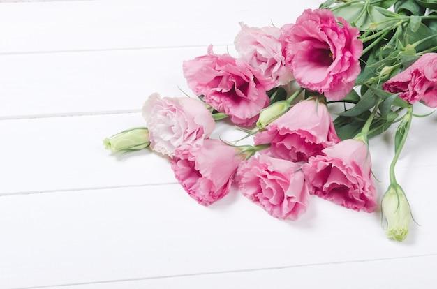 Verse roze eustomabloemen op witte houten