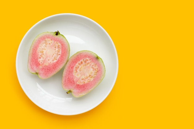 Verse roze guave in witte plaat op gele achtergrond.
