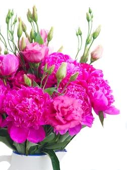 Verse roze pioen en eustoma bloemen boeket in blauwe pot geïsoleerd op een witte achtergrond