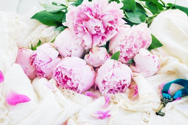 Verse roze pioenbloemen op vintage kanten kledingstuk