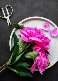 Verse roze pioenroos bloemen op een betonnen plaat met kopieerruimte op zwarte ondergrond plat lag