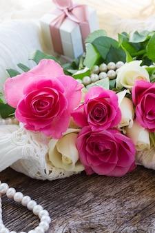 Verse roze roze bloem op kant met geschenkdoos en parels
