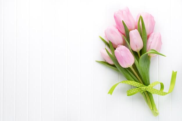 Verse roze tulp bloemen boeket op plank voor houten muur.