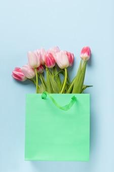 Verse roze tulpen in groene papieren zak op blauw.