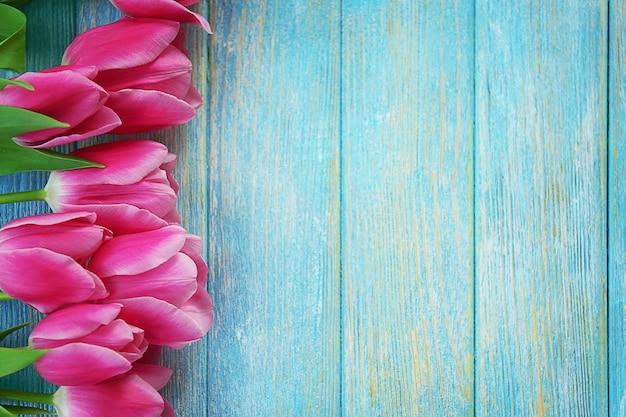 Verse roze tulpen op een houten tafel, bovenaanzicht