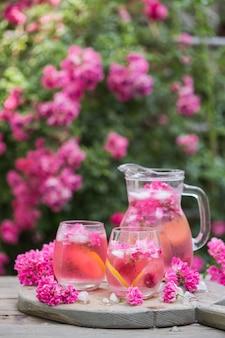Verse rozenlimonade met ijs en verse rozen over natuurlijke tuin