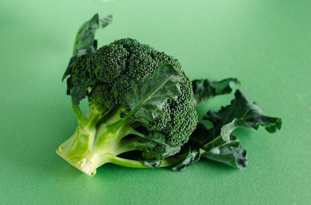 Verse ruwe broccoli op groene achtergrond. biologisch voedsel concept