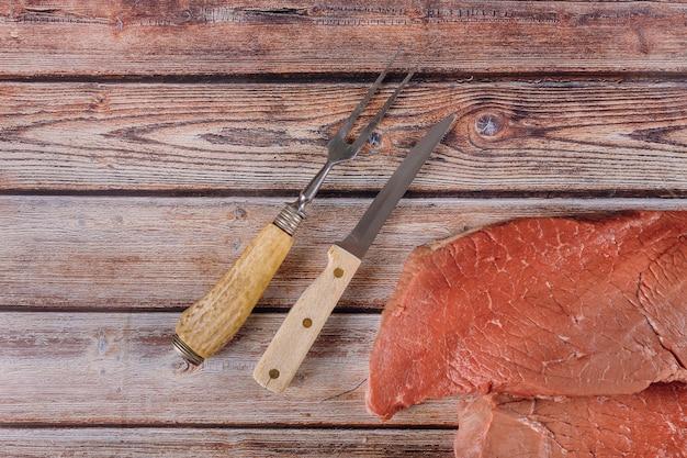 Verse ruwe rundvleeslapjes vlees met mes op houten lijst