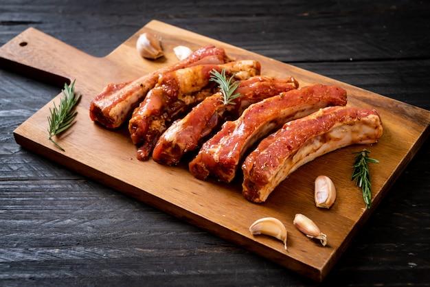 Verse ruwe varkensvleesribben klaar voor het roosteren met ingrediënten
