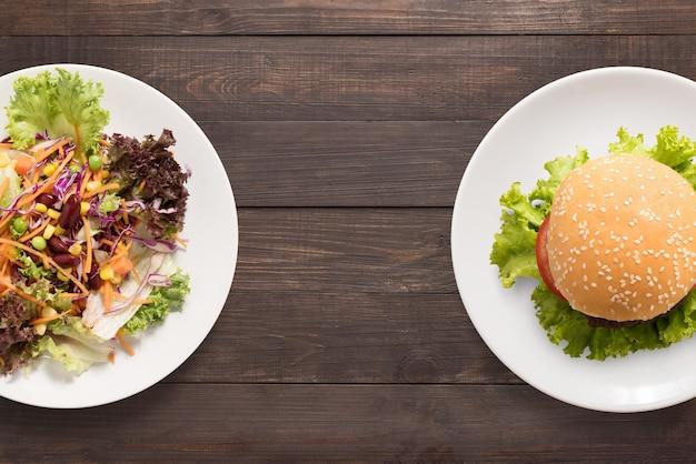 Verse salade en hamburger op de houten achtergrond. contrastrijk eten