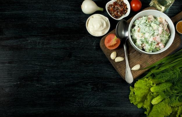 Verse salade in een bord op een donkere ondergrond. knoflook, tomaat, komkommer, dille en ui in een schaal met een donker oppervlak.
