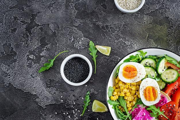 Verse salade. kom met verse rauwe groenten - komkommer, tomaat, watermeloenradijs, sla, rucola, maïs en gekookt ei. gezond eten. vegetarische boeddha schaal. bovenaanzicht plat leggen