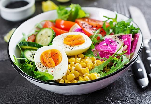 Verse salade. kom met verse rauwe groenten - komkommer, tomaat, watermeloenradijs, sla, rucola, maïs en gekookt ei. gezond eten. vegetarische boeddha schaal.