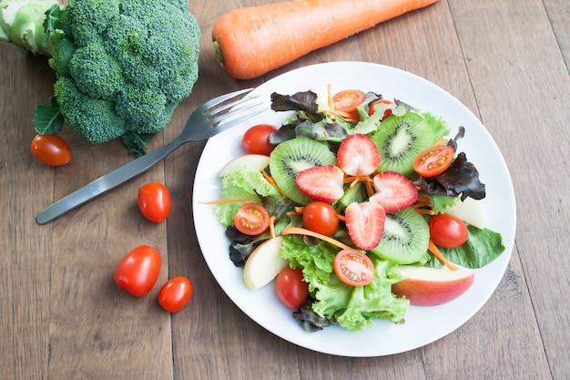 Verse salade met aardbeien, kiwi, tomaten en appels op een witte plaat