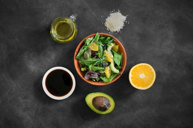 Verse salade met ingrediënten op de zwarte tafel