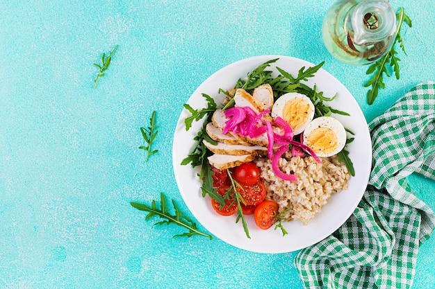 Verse salade. ontbijtkom met havermout, kipfilet, tomaat, rode ui en gekookt ei. gezond eten. vegetarische boeddha schaal. bovenaanzicht, plat gelegd