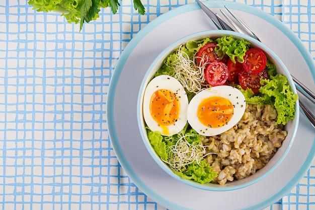 Verse salade. ontbijtkom met havermout, tomaten, sla, microgreens en gekookt ei. gezond eten. vegetarische boeddha schaal. bovenaanzicht, plat lag