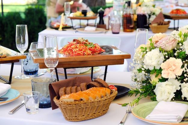 Verse salade op een houten plaat op een banketlijst die met elegant bloemenboeket wordt verfraaid.