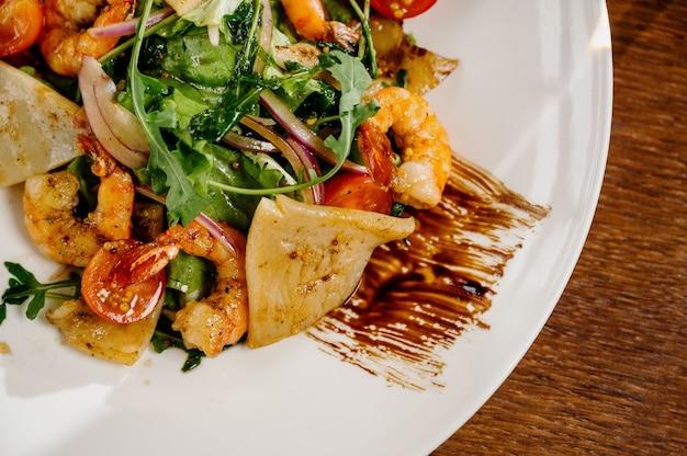 Verse salade plaat met garnalen, tomaat en gemengde greens op houten oppervlak close-up