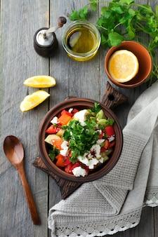 Verse salade shopska van gebakken paprika, tomaat, ui, komkommer, peterselie, dille en fetakaas in een keramische kom