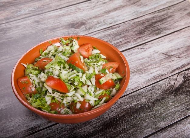 Verse salade van tomaten, komkommers en kool is op een houten tafel