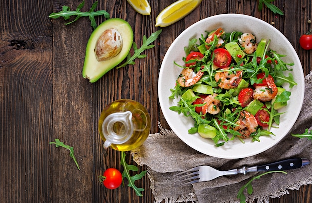 Verse saladekom met garnalen, tomaat, avocado en arugula op houten lijst dichte omhooggaand. gezond eten. schoon eten. bovenaanzicht plat leggen.