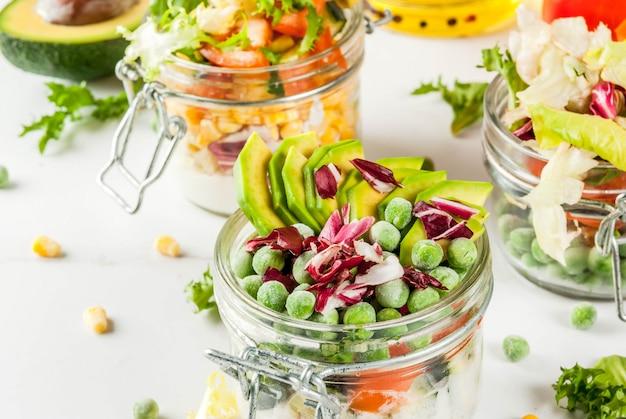 Verse salades in pot met verse groenten en gezonde dressings, op witte marmeren tafel,