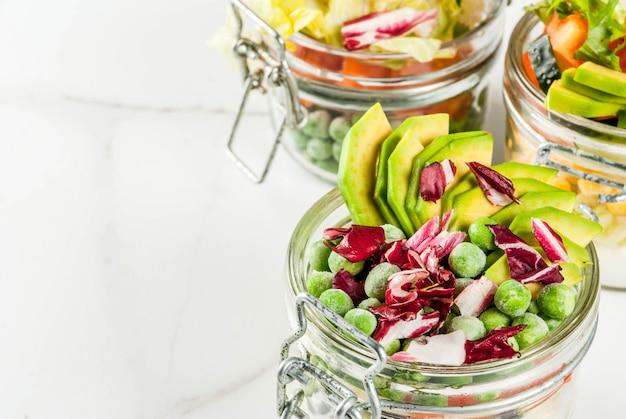 Verse salades in pot met verse groenten en gezonde dressings
